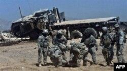 Binh sĩ NATO trợ giúp một đồng đội bị thương trong vụ nổ bom vệ đường ở Kandahar, miền nam Afghanistan, ngày 12/10/2010. Một vụ nổ trên một máy bay trực thăng đã giết chết 1 người và làm bị thương 8 người khác ngay sau hạ cánh tại một căn cứ ở tỉnh Kunar
