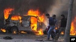 21일 시리아 관영 SANA 통신이 배포한 사진. 시리아 수도 다마스쿠스에서 연쇄 폭탄공격이 발생한 가운데, 폭탄 폭발 후 부상자를 옮기는 시리아 보안요원들이 부상자를 옮기고 있다.