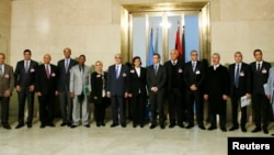 Special Representative of the Secretary-General for Libya and Head UNSMIL Bernardino Leon (C) poses with delegates for a group photograph after a news conference at the Palais des Nations in Geneva, Jan. 14, 2015.