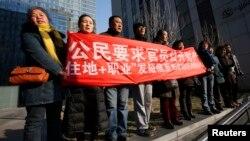 Sledbenici Šu Žijonga, istaknutog advokata za odbranu ljudskih prava uzvikuju slogane nedaleko od suda gde mu se sudi, Peking 22. januar 2014.