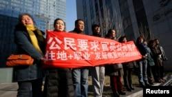 Para pendukung Xu Zhiyong, salah satu aktivis hak asasi manusia di China yang paling terkemuka, meneriakkan slogan-slogan di luar gedung pengadilan di Beijing (22/1). (Reuters/Kim Kyung-Hoon)