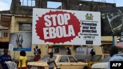 """FILES - People walking past a billboard reading """"Stop Ebola"""" in Freetown, Sierra Leone, Nov. 7, 2014."""