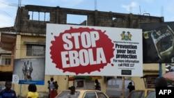 """FILE - People walking past a billboard reading """"Stop Ebola"""" in Freetown, Sierra Leone, Nov. 7, 2014."""