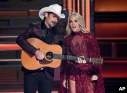 Hosts Brad Paisley, left, and Carrie Underwood appear during the opening of the 51st annual CMA Awards at the Bridgestone Arena, Nov. 8, 2017, in Nashville, Tennessee.