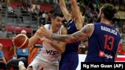 Argentinski košarkaš Luis Skola u duelu sa Vladimirom Lučićem i Miroslavom Raduljicom (Foto: AP/Ng Han Guan)