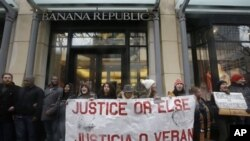 Protesters block an entrance to Banana Republic store on Friday, Nov. 27, 2015, in Chicago as community activists and labor leaders hold a demonstration responding to the release of a video showing an officer fatally shooting Laquan McDonald. (AP Photo/Nam Y. Huh)
