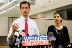 FILE - Then-New York mayoral candidate Anthony Weiner speaks during a news conference alongside his wife Huma Abedin in New York.
