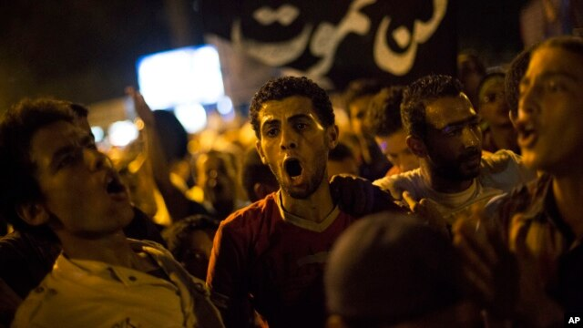 "Supporters of Egypt's ousted President Mohammed Morsi chants slogans against the Egyptian Army after ""Iftar"" during a protest near Cairo University in Giza, Egypt, Aug. 4, 2013."