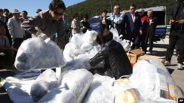 North Korean defectors carry plastic bags full of leaflets denouncing North Korea for canceling a planned reunion of Korean families, to be attached to balloons during a rally near the Unification Observation Post in Paju, South Korea, Oct. 4, 2013.