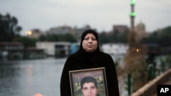 "Amel Shaker holds a portrait of her 25-year-old son Ahmed, who was fatally shot in the back on the ""Friday of Rage,"" one of the bloodiest days of Egypt's 2011 uprising against longtime autocrat Hosni Mubarak, in Cairo, Egypt."