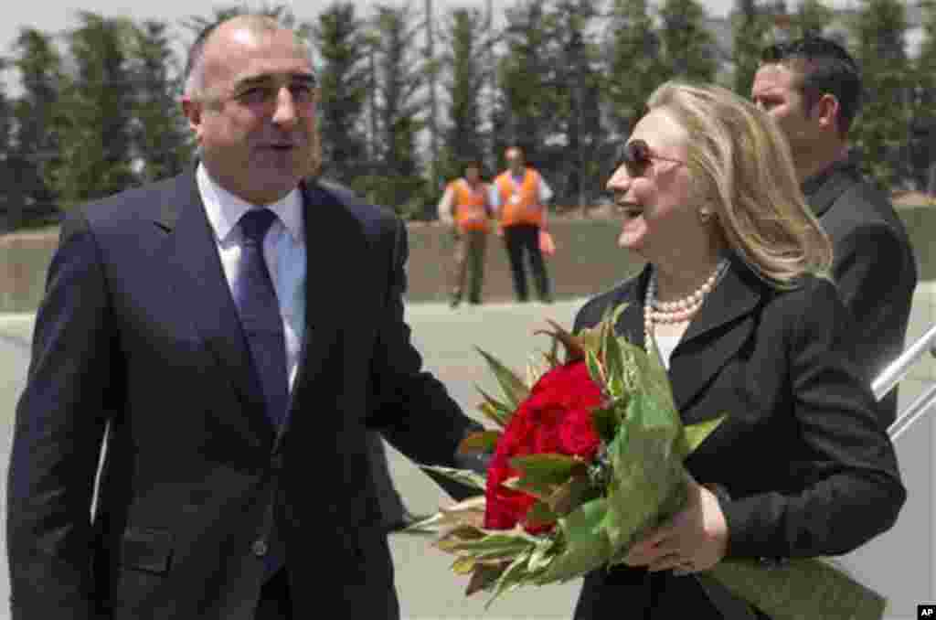 Azeri Foreign Minister Elmar Mammadyarov, left, greets US Secretary of State Hillary Rodham Clinton Wednesday June 6, 2012 upon her arrival the Heydar Aliyev International Airport in Baku, Azerbaijan. Clinton has embarked on a tour of the South Caucasus