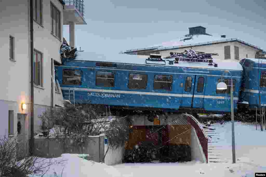 A local train derails and crashes into a residential building in Saltsjobaden outside Stockholm, Sweden, January 15, 2013.
