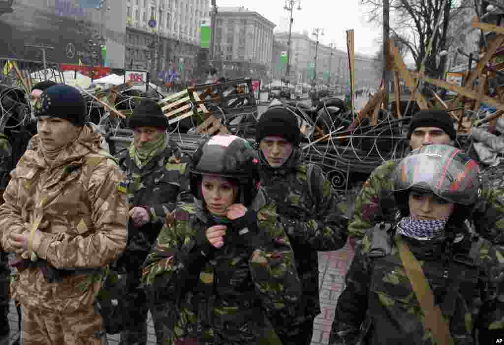 Pro-European Union activists stand in front of a barricade of their tent camp to protect it, Kyiv, Ukraine, Jan. 18, 2014.
