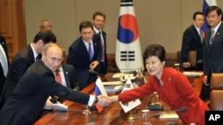 ولادیمیر پوتین، رئیس جمهوری روسیه با خانم پارک کوئن های، همتای کره جنوبی خود دست میدهد