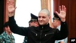 Tokoh oposisi kiri Rusia, Sergei Udaltsov melambai kepada pendukungnya dalam sidang pengadilan di Moskow Juli 2014 (foto: dok).