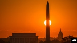 The rising sun passes behind on the Washington Monument early in the morning, Sept. 14, 2016, in Washington on what is expected to be another 90 degree day in the Nation's Capitol.
