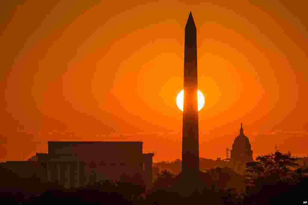 ព្រះអាទិត្យរះពីក្រោយវិមាន Washington Monument ក្នុងរដ្ឋធានីវ៉ាស៊ីនតោន។