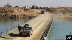 ກຳລັງຮັກສາຄວາມປອດໄພຂອງອີຣັກ ຂ້າມຂົວ ທີ່ແມ່ນ້ຳ Euphrates ສ້າງໂດຍໜ່ວຍວິສະວະກອນກອງທັບ ຫຼັງຈາກ ກຸ່ມລັດອິສລາມໄດ້ທຳລາຍຂົວຕ່າງໆ ໄປສູ່ເຂດໃຈກາງ ເມືອງ.