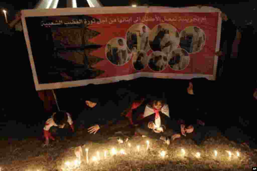 Bahraini anti-government protesters sit with candles lit in memory of those killed, as they gather in Pearl Square, in Manama, Bahrain, February 19, 2011, the focal point of bloody anti-regime demonstrations. (AFP Image)