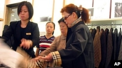 Local shoppers take a look at clothing in a Burberry store on in Shanghai, China. (file photo)
