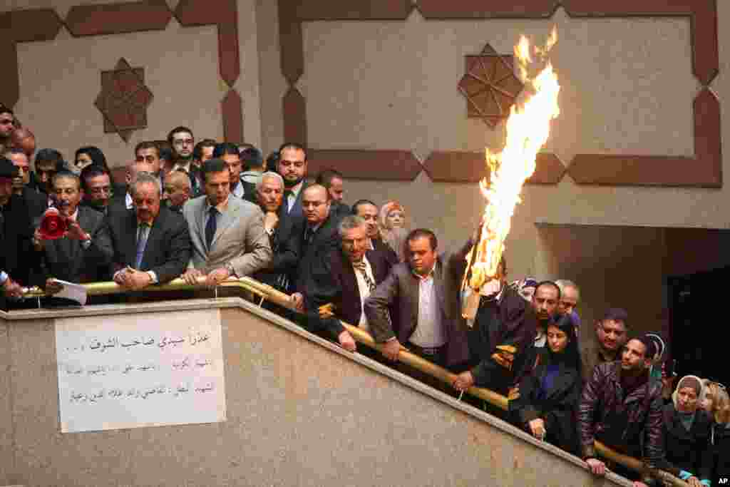 Jordanian lawyers and judges burn a representation of the Israeli flag during a strike inside the Palace of Justice in Amman, protesting the killing of Jordanian judge Raed Zueter by Israeli soldiers. The protesters demand the deportation of the Israeli ambassador and the immediate release of Ahmed Daqamseh. Daqamseh is serving a life sentence for killing Israeli schoolgirls in 1997 during an outing near Jordan's northwestern border with Israel.