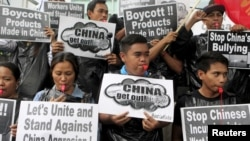 Protesters from the Socialista National Confederation of Labor activist group blow whistles as a part of the noise barrage during a rally over the South China Sea disputes with China, outside the Chinese Consulate in Makati City, Manila, July 10, 2015.