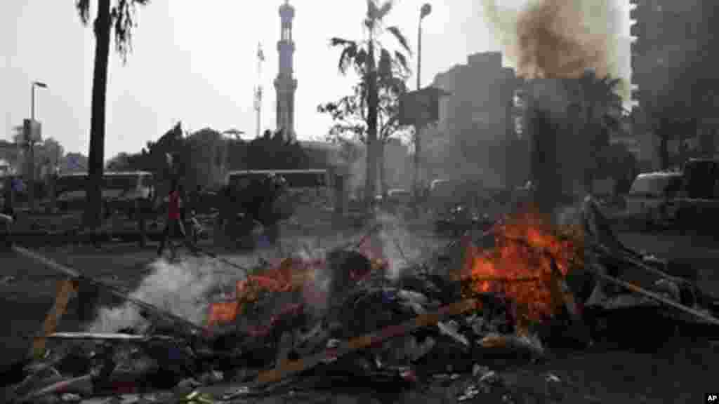 The remains of tents burn outside Rabaah al-Adawiya mosque, where supporters of Egypt's ousted President Morsi had a protest camp, Aug. 15, 2013.