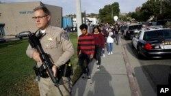 Polisi bersenjata mengamankan para siswa saat terjadi penembakan di Saugus High School di Santa Clarita, California, AS hari Kamis (14/11).