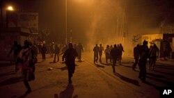 Des manifestants fuyant les tirs de gaz lacrymogène à Dakar le 27 janvier 2012
