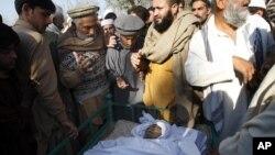 Dân làng đứng cạnh thi hài nhân viên y tế Hilal Khan, bị giết