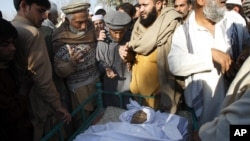 Villagers look at the body of health worker Hilal Khan, who was killed by gunmen in Wahidgari, outside of Peshawar, Pakistan, Dec. 20, 2012.