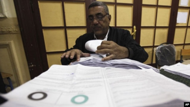 An official examines votes from ballot boxes after the polls closed in Cairo, March 19, 2011