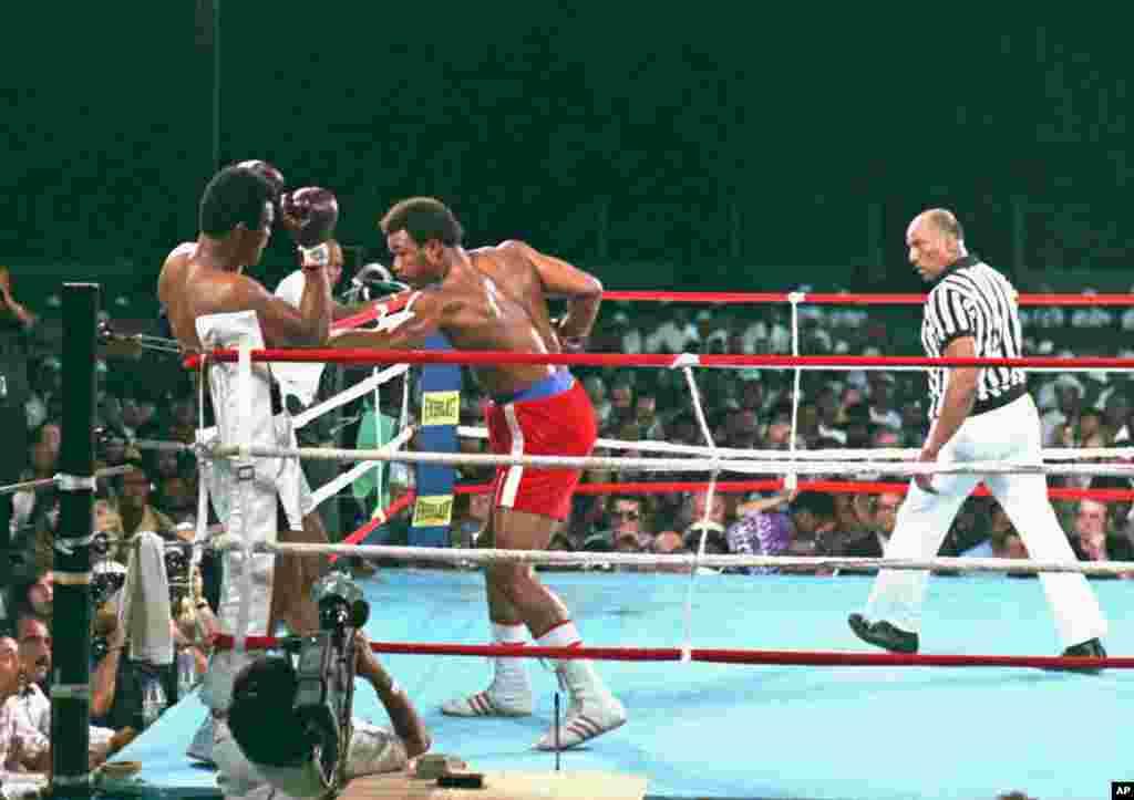 George Foreman, tengah, melepaskan pukulan ke arah Muhammad Ali saat pertandingan di Zaire, Afrika, 30 Oktober 1974. Wasit Zack Clayton berada di sebelah kanan. Ali menang KO pada ronde kedelapan. (AP PHOTO)