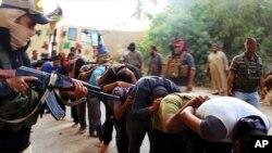 지난 6월 이슬람 수니파 무장반군 '이슬람국가'가 생포한 이라크 정부군 병사들을 향해 총을 겨누고 있다.
