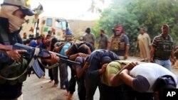Chiến binh Nhà nước Hồi giáo chĩa súng vào các binh sĩ Iraq bị bắt. (Ảnh tư liệu)