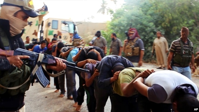 FILE - This image posted on a militant website on June 14, 2014, which has been verified and is consistent with other AP reporting, appears to show militants from the al-Qaida-inspired Islamic State leading away captured soldiers.