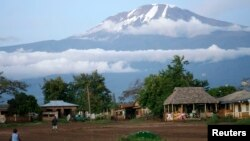 FILE - Houses sit near the foot of Mount Kilimanjaro, one of the country's top tourist draws, in Tanzania's Hie district.