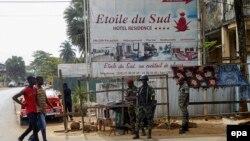 Des soldats ivoiriens patrouillent à l'extérieur de l'Etoile du Sud hôtel à côté de quelques passants à Grand Bassam, Côte-d'Ivoire, 14 mars 2016. epa/ LEGNAN KOULA