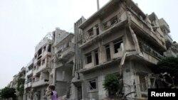 Dečak na biciklu ispred teško oštećenih zgrada u sirijskom gradu Homsu, 24. maja 2013.