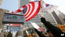 Para demonstran di Seoul melambai-lambaikan bendera AS dan Korea Selatan dalam aksi yang mendukung sistem pertahanan misil AS, THAAD (15/2). (AP/Ahn Young-joon)
