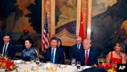 El presidente Donald Trump y el presidente chino Xi Jinping, con sus esposas, la primera dama Melania Trump y la primera dama china Peng Liyuan, están sentados durante una cena en Mar-a-Lago el jueves 6 de abril de 2017 en Palm Beach.