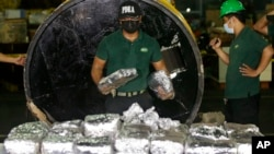 "FILE - A member of the Philippine Drug Enforcement Agency, PDEA, collects packs of Methamphetamine Hydrochloride also known as ""Shabu"" which they found hidden inside a steel cylinder in one of the biggest drug hauls in Manila, Philippines, on Aug. 7, 2018."
