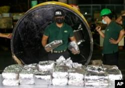 "Seorang anggota Badan Pemberantasan Narkoba Filipina, PDEA, mengumpulkan bungkusan Metamfetamin Hidroklorida yang juga dikenal sebagai ""Shabu"" yang mereka temukan tersembunyi di dalam silinder baja di salah satu penyelundupan narkoba terbesar di Manila, Filipina, pada 7 Agustus 2018. ( Foto: AP)"