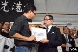 香港大學校友關注組召集人葉建源(左)向港大校委會主席梁智鴻遞交超過1,500名校友的聯署聲明,要求盡快確認副校長物色委員會的建議。(美國之音湯惠芸)
