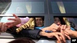 Công dân Bắc Triều Tiên trên xe buýt nắm tay thân nhân Nam Triều Tiên trong lúc chia tay sau cuộc đoàn tụ gia đình ở Núi Kim Cương, ngày 25/2/2014.