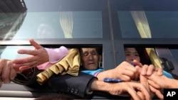 Warga Korea Utara di dalam bus memegang tangan-tangan kerabatnya dari Korea Selatan dalam reuni di Gunung Diamond, Korea Utara, 25 Februari 2014. (AP/Yonhap, Lee Ji-eun)