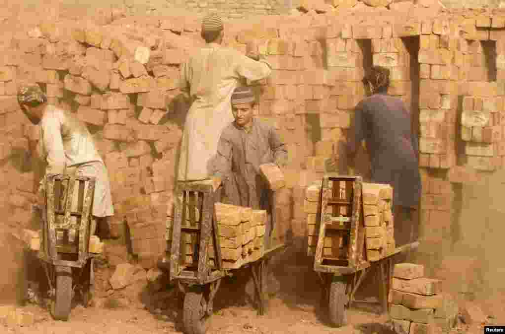 Laborers move baked bricks from an oven at a kiln on outskirts of Peshawar, Pakistan.