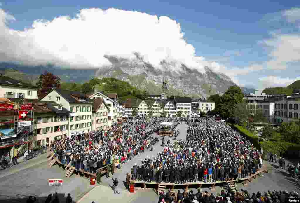People hold up their voting cards during the annual Landsgemeinde meeting at the Zaunplatz square, in the eastern Swiss town of Glarus. Glarus is one of Switzerland's two remaining Landsgemeinden, a 700-year tradition of an open-air assembly in which citizens can make key political decisions directly by raising their hands.