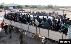 Migrants ride in a truck to a detention center in the coastal city of Sabratha, Libya, Oct. 7, 2017.