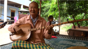 Sitting on a wooden bed in Tropeang Kok village, Takeo province, Brach Chhoun uses both hands, full of wrinkles, to play.